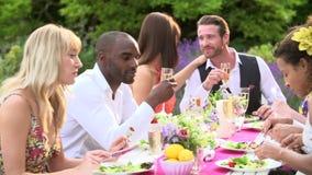 Amigos que disfrutan del partido de cena al aire libre junto almacen de video