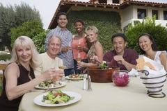 Amigos que disfrutan del partido de cena en jardín Fotografía de archivo