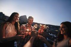 Amigos que disfrutan del partido del tejado con las bengalas Imagen de archivo