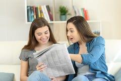 Amigos que encontram notícias surpreendentes em um jornal imagem de stock