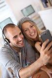 Amigos que escuchan la música y que toman el selfie Imagen de archivo libre de regalías
