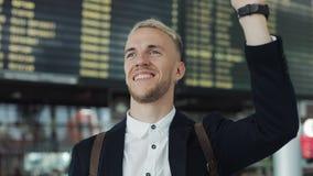 Amigos que esperan del hombre de negocios joven atractivo cerca de la pantalla del tablero del calendario en el aeropuerto Él agi almacen de video