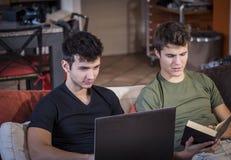 Amigos que estudian con el libro y el ordenador portátil Foto de archivo libre de regalías
