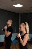 Amigos que exercitam com os sinos da chaleira no gym Imagens de Stock Royalty Free