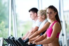 Amigos que exercitam em uma escada rolante no gym moderno brilhante Fotografia de Stock