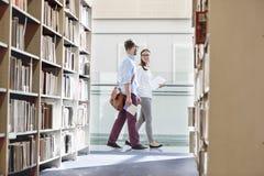 Amigos que falam ao andar na biblioteca da universidade imagem de stock royalty free