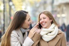 Amigos que falam no telefone na rua no inverno imagem de stock royalty free