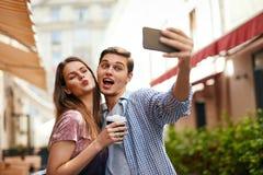 Amigos que fazem a foto no telefone celular na rua fotografia de stock royalty free