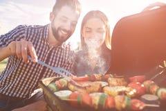 Amigos que fazem o assado e que têm o almoço na natureza Acople ter o divertimento ao comer e ao beber em um piquenique - feliz fotografia de stock