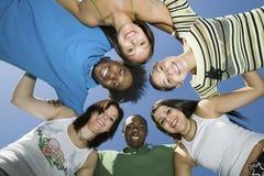 Amigos que forman el grupo contra el cielo azul Foto de archivo