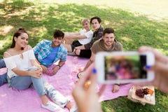 Amigos que fotografían por smartphone en la comida campestre Foto de archivo libre de regalías