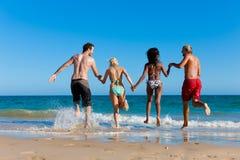 Amigos que funcionam em férias da praia foto de stock royalty free