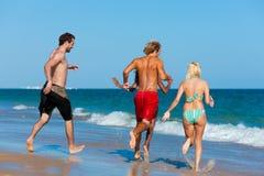 Amigos que funcionam em férias da praia Fotos de Stock