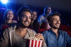 Amigos que gozan en el cine Imagenes de archivo