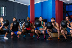 Amigos que guardam a bola do exercício no gym fotos de stock royalty free