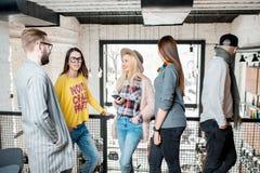 Amigos que hablan durante la rotura en la sala de conferencias Foto de archivo libre de regalías