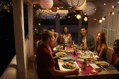Amigos que hablan en un partido de cena en un patio, Ibiza, España Fotografía de archivo