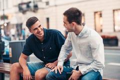 Amigos que hablan junto en un banco en la ciudad Foto de archivo