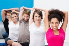 Amigos que hacen aeróbicos juntos en el gimnasio Foto de archivo libre de regalías