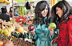 Amigos que hacen compras de las manzanas del mercado Fotos de archivo