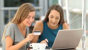 Amigos que hacen compras en línea pagando con la tarjeta almacen de video