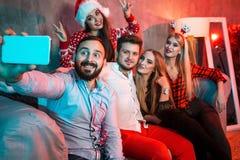 Amigos que hacen el selfie mientras que celebra la Navidad o la Noche Vieja en casa Fotografía de archivo