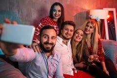 Amigos que hacen el selfie mientras que celebra la Navidad o la Noche Vieja en casa Fotos de archivo libres de regalías