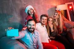 Amigos que hacen el selfie mientras que celebra la Navidad o la Noche Vieja en casa Imagen de archivo