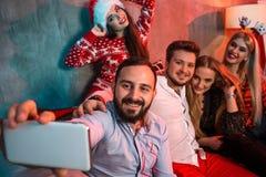 Amigos que hacen el selfie mientras que celebra la Navidad o la Noche Vieja en casa Imagenes de archivo