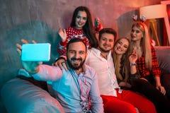 Amigos que hacen el selfie mientras que celebra la Navidad o la Noche Vieja en casa Fotografía de archivo libre de regalías
