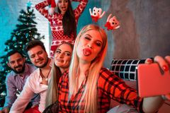 Amigos que hacen el selfie mientras que celebra la Navidad o la Noche Vieja en casa Imágenes de archivo libres de regalías