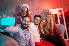 Amigos que hacen el selfie mientras que celebra la Navidad o la Noche Vieja en casa Foto de archivo libre de regalías