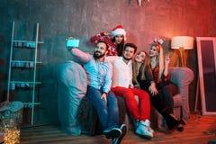 Amigos que hacen el selfie mientras que celebra la Navidad o la Noche Vieja en casa Imagen de archivo libre de regalías