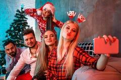 Amigos que hacen el selfie mientras que celebra la Navidad o la Noche Vieja en casa Fotos de archivo