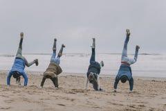 Amigos que hacen posiciones del pino en una playa del invierno Imagen de archivo libre de regalías