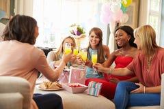 Amigos que hacen una tostada con Juice At Baby Shower anaranjado imagenes de archivo