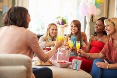 Amigos que hacen una tostada con Juice At Baby Shower anaranjado Fotografía de archivo