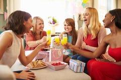 Amigos que hacen una tostada con Juice At Baby Shower anaranjado imagen de archivo libre de regalías