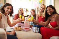 Amigos que hacen una tostada con Juice At Baby Shower anaranjado fotografía de archivo libre de regalías
