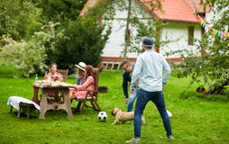 Amigos que jogam o futebol com o cão no jardim do verão Foto de Stock Royalty Free