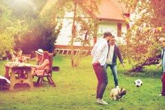 Amigos que jogam o futebol com o cão no jardim do verão Imagem de Stock Royalty Free