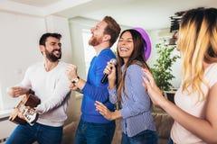 Amigos que jogam o karaoke em casa Conceito sobre a amizade, o home entertainment e os povos foto de stock royalty free