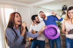 Amigos que jogam o karaoke em casa Conceito sobre a amizade, o home entertainment e os povos imagem de stock royalty free