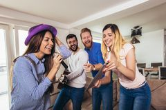 Amigos que jogam o karaoke em casa Conceito sobre a amizade, o home entertainment e os povos fotografia de stock royalty free