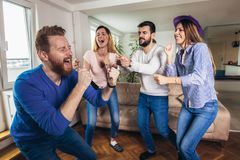 Amigos que jogam o karaoke em casa Conceito sobre a amizade, o home entertainment e os povos fotos de stock
