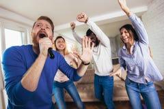 Amigos que jogam o karaoke em casa Conceito sobre a amizade, o home entertainment e os povos imagens de stock royalty free