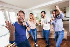 Amigos que jogam o karaoke em casa Conceito sobre a amizade, o home entertainment e os povos imagem de stock