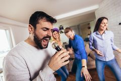 Amigos que jogam o karaoke em casa Conceito sobre a amizade, o home entertainment e os povos fotos de stock royalty free