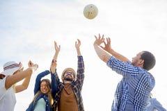 Amigos que jogam o voleibol Imagem de Stock