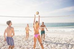 Amigos que jogam o voleibol da praia fotografia de stock royalty free